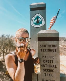 A woman stands with a cigar next to the southern terminus monument of the Pacific Crest Trail.