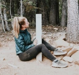 A girl sits on the ground next to a trail sign post.