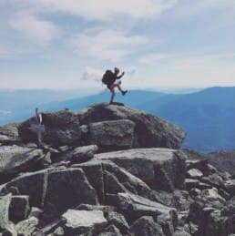 A hiker with a backpack poses on top of a rock pile.