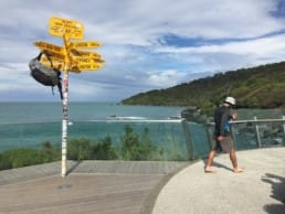 A man walks away from the Te Araroa sign that has his backpack hanging on it.