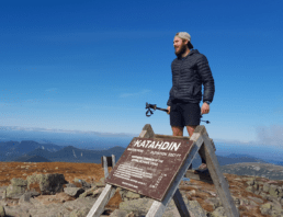 A hiker stands on top of the Mount Katahdin sign on the Appalachian Trail.