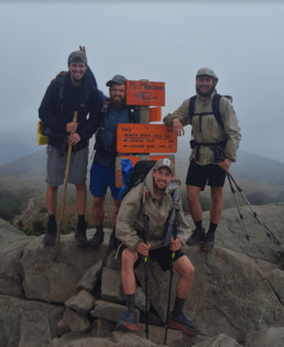 A group of guys hiking pose by a trail sign on the Appalachian Trail.
