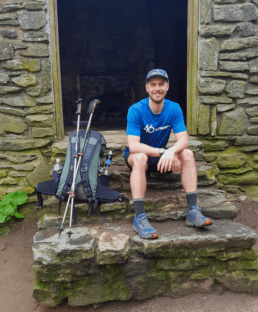 A guy hiking the Appalachian Trail sits on the steps of a building with his backpack next to him.