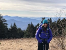 A girl hiking the Appalachian Trail stands smiling with the mountains and trees behind her.