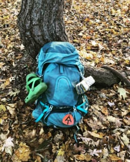 A thru-hiking backpack propped up against a tree.