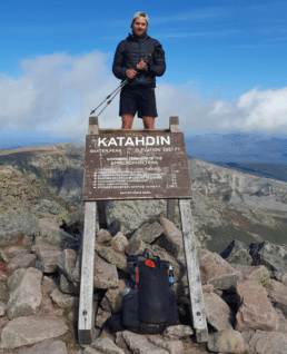 A hiker stands on the Mount Katahdin sign on the Appalachian Trail.