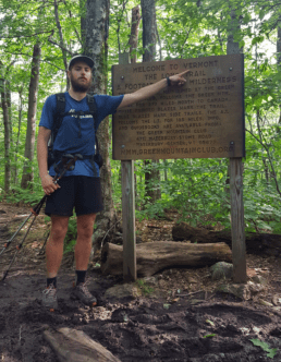 A hiker stands in the woods pointing at an Appalchian Trail sign.