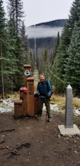 A man stands next to the northern terminus of the Pacific Crest Trail.