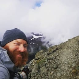 A man with a beard smiling on a mountain with clouds behind him.