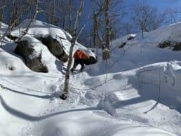 A hiker climbing a steep snowy gully in Camden Hills State Park