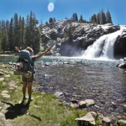 A woman hiker standing with her arms up in front of a waterfall.