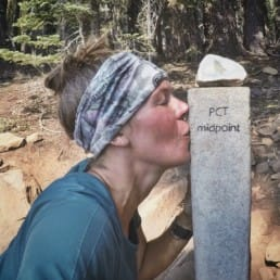 A woman hiker kissing a Pacific Crest Trail sign post.