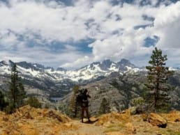 A hiker stands with a view of the mountain s behind.
