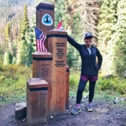 A woman hiker standing next to the northern terminus on the Pacific Crest Trail.