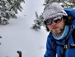 A hiker in the snow with a beanie and sunglasses on.