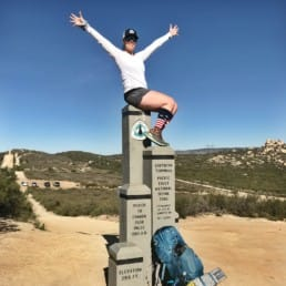 A hiker sitting on top of the Pacific Crest Trail southern terminus.