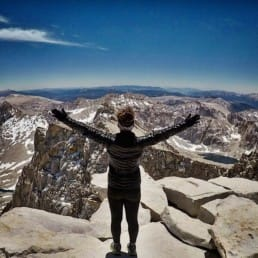 A woman hiker standing with her arms up in the air looking at the mountains.