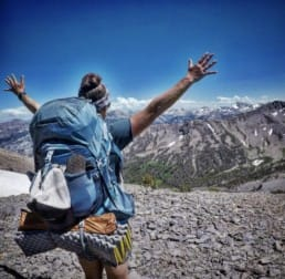 A girl hiker standing with her arms up looking out at the mountains.