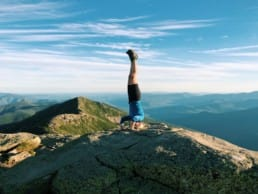 A woman doing a headstand on a hill with beautiful mountains behind her.