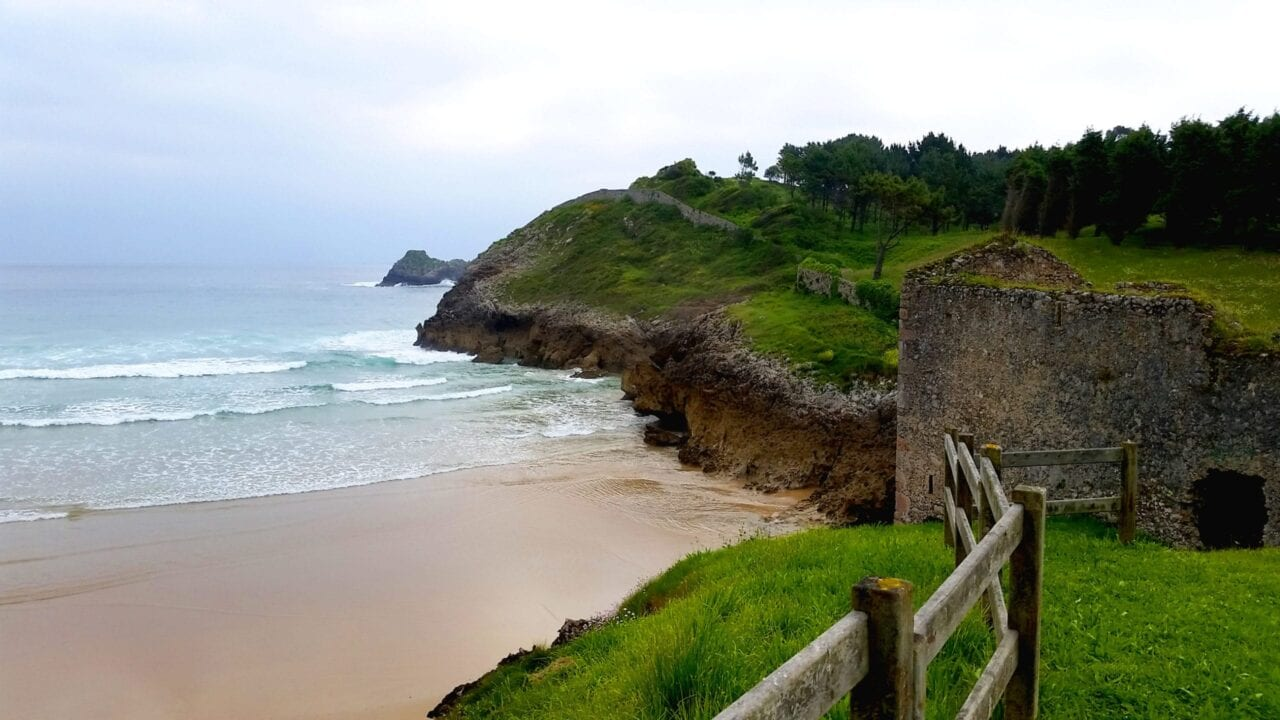 A stone ruin stands in a green field next to a sandy beach and the ocean.