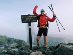 A woman hiker standing next to the Mt Washington Summit sign, holding her trekking poles up.