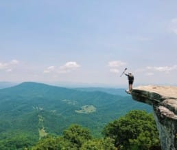 A woman standing at the edge of a rock cliff on the Appalachian Trail.