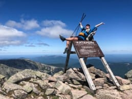 A woman sitting on the Mt Katahdin sign with her arms and leg in the air.