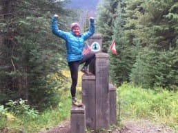 A woman standing on the northern terminus of the Pacific Crest Trail.