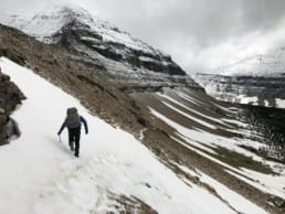 A hiker on a snowy mountain hillside.