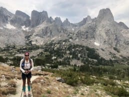 A hiker stands on a trail with beautiful mountains in the background.