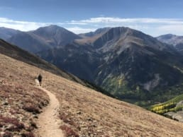 A hiker on a trail with big mountains in the distance.