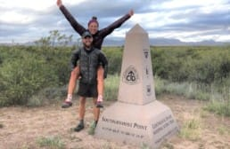 A man giving his wife a piggy back ride next to the Continental Divide Trail terminus.