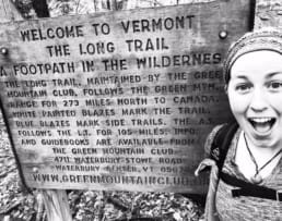 A woman smiles next to a Long Trail sign.
