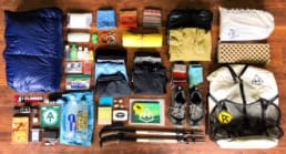 A hiker lays out all of her hiking gear on the floor to display everything she's brining on her thru-hike.