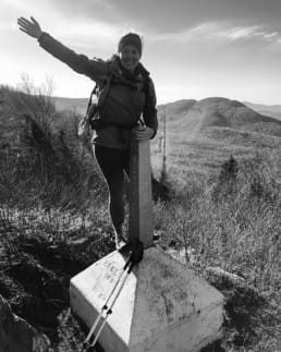 A hiker stands on a trail terminus with her arm in the air.