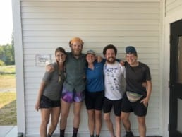 A group of hiker friends hugging.