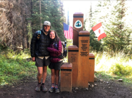 A man and woman stand hugging next to the northern terminus of the Pacific Crest Trail.