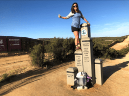 A woman stands on the southern terminus of the Pacific Crest Trail.