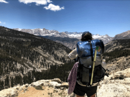 A hiker stands with her backpack and bear canister strapped to her back as she looks over the mountains.