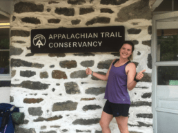 A woman stands with her thumbs up next to the Appalachian Trail Conservancy sign.
