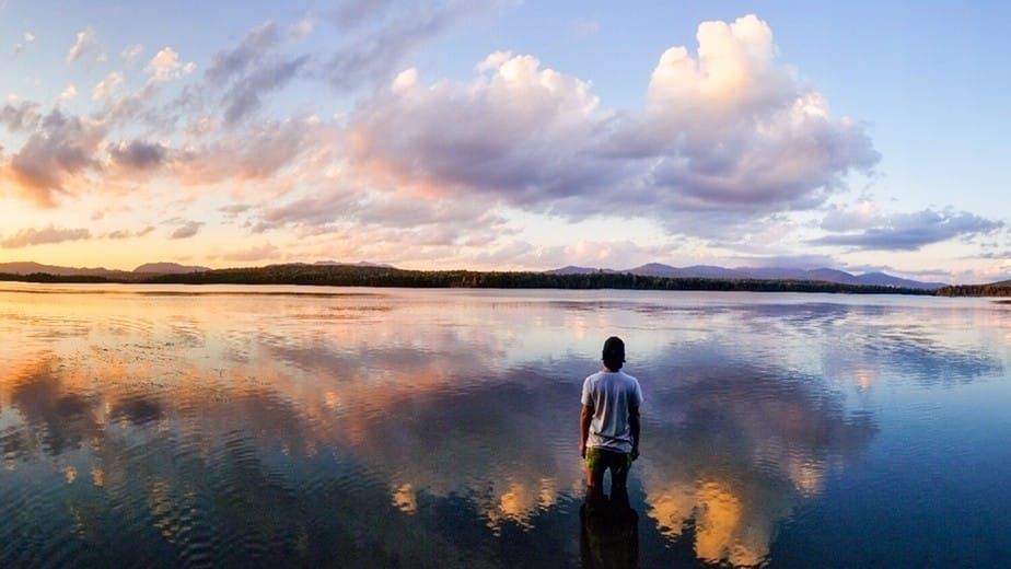 A man stands in front of a lake with a sunset reflecting in the water.