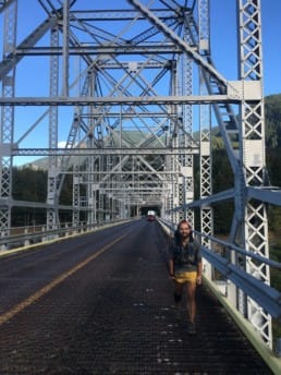 A hiker walking across a bridge.
