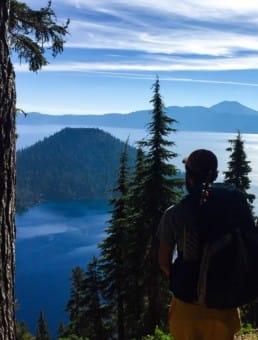 A hiker standing with his backpack on looking out at a mountain and lake below.
