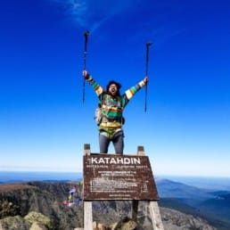 A hiker standing on the sign on top of Mount Katahdin holding his trekking poles in the air.