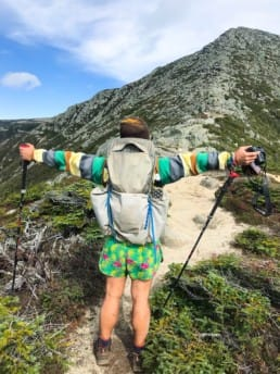 A hiker standing on a trail with his arms out holding trekking poles.