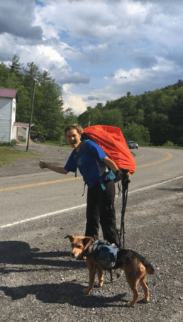 A woman hitch-hiking with her dog on the side of the road.