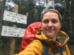 A woman in front of an Appalachian Trail sign.