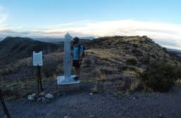 A hiker standing on the southern terminus of the Arizona Trail.