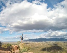 A hiker standing on a big boulder in the distance with a scenic background.