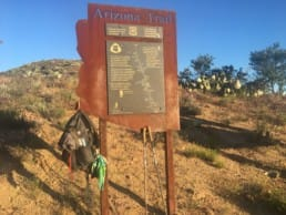 An Arizona Trail sign with a backpack hanging off of it.